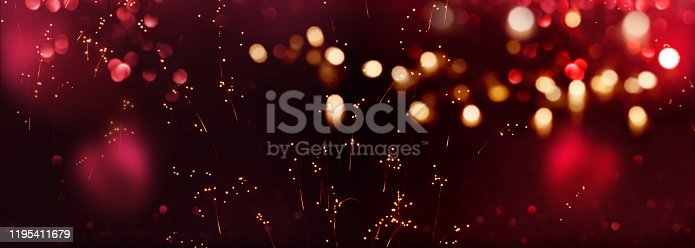 Dark festive celebration background with red and golden bokeh for valentines day and new year greetings.
