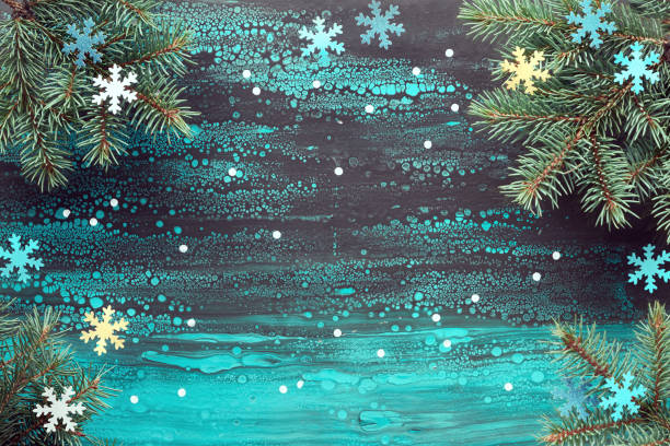 Festive Christmas background with fir twigs and paper decorations on fluid art background, copy-space stock photo