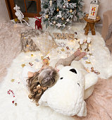 A female sits on rugs in front of the Christmas tree with Christmas decorations and festive ornaments all around  her