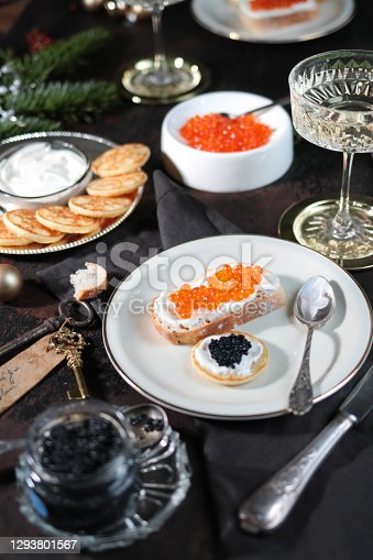 Festive Christmas Table with Caviar Blinis and Champagne in dark elegant table scene