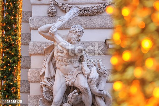 Festive cityscape - view of the sculpture of Hercules with the Lernaean Hydra on the St. Michael's Wing of the Hofburg during the Christmas days in the city of Vienna, Austria