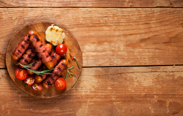 Festive cocktail sausages wrapped in crispy smoked bacon commonly known as 'Pigs in Blankets' on wooden background stock photo