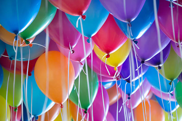 festive, colorful balloons with helium attachment to the white ribbons stock photo