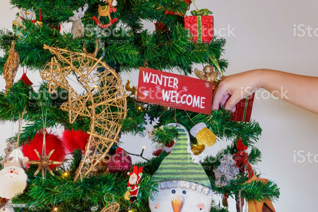 Festive colorful decorations before an illuminated artificial Christmas tree with winter welcome message hanging from a brunch. stock photo