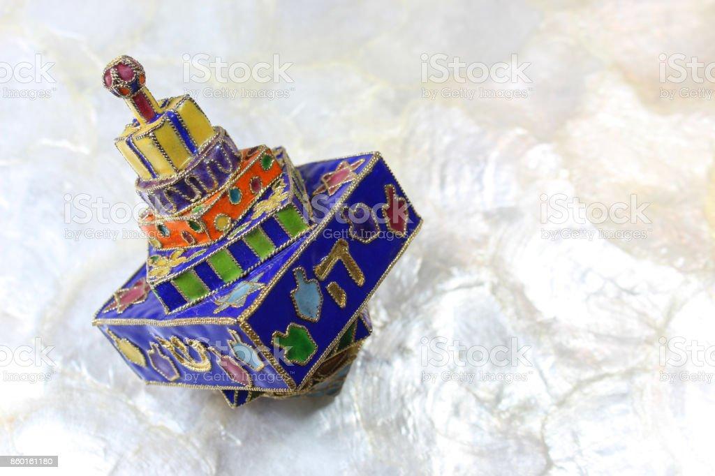 Festive colorful enameled Hanukkah dreidel on a soft white background stock photo
