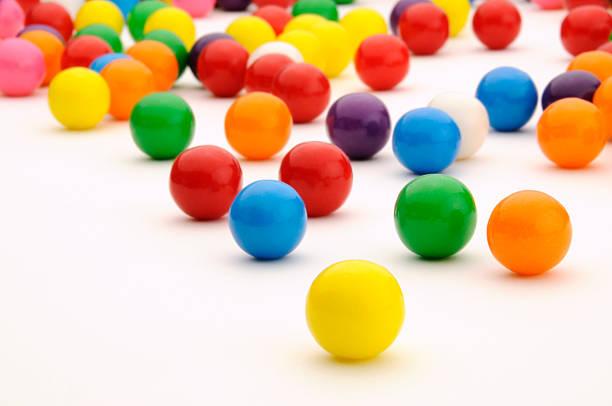 festive, colorful gum balls candy rolling, white background surface - sakız şekerleme stok fotoğraflar ve resimler