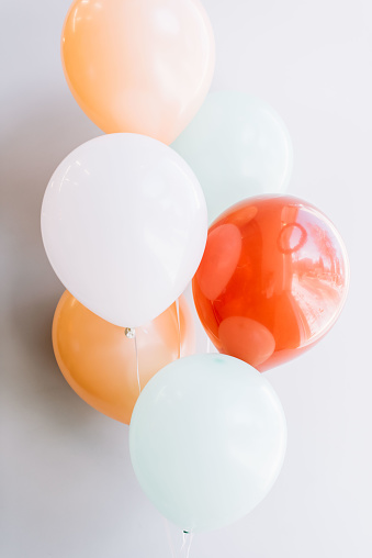festive colourful ballons on the grey wall background