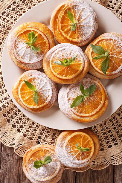 festive cookies with oranges closeup on a plate. vertical - spitzenkekse stock-fotos und bilder