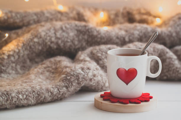 festive cup of tea with a smoke and a red heart over the knitted plaid - february stock photos and pictures