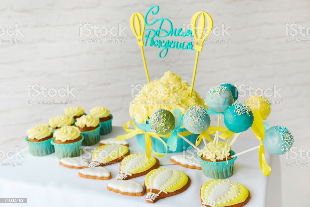 Festive decor candy bar birthday party with cookies and cupcakes....