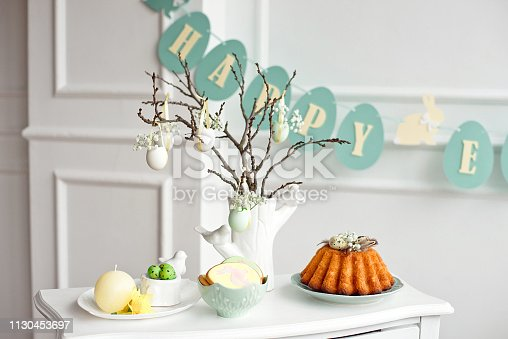 istock Festive decoration of the Easter table, a vase with a branch and decorations from flowers and eggs, biscuits with rabbit, Easter cake and sweets. 1130453697