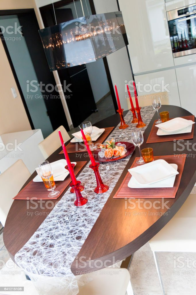 Festive modern dining table with dishes, glasses, cadles and...