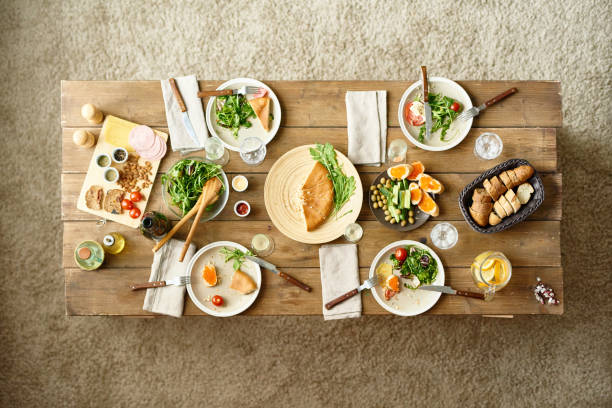 Festive Dinner Table Above view of wooden dinner table with half-eaten dishes left on it, no people thanksgiving leftovers stock pictures, royalty-free photos & images