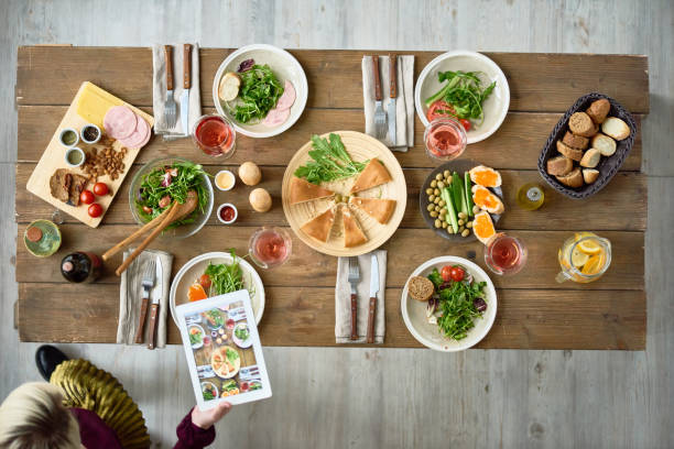 Festive Dinner Table Above view of wooden dinner table with half-eaten dishes left on it, and young woman taking food-photography using digital tablet thanksgiving leftovers stock pictures, royalty-free photos & images