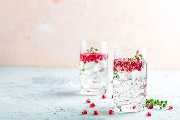 Festive drinks, gin and tonic pomegranate cocktail or detox water with ice stock photo