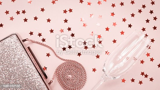1078252566 istock photo Festive evening golden clutch and champagne glass with star sprinkles on pink. Holiday and celebration background. Luxury accessories and party concept . Living coral theme - color of the year 2019 1081152132