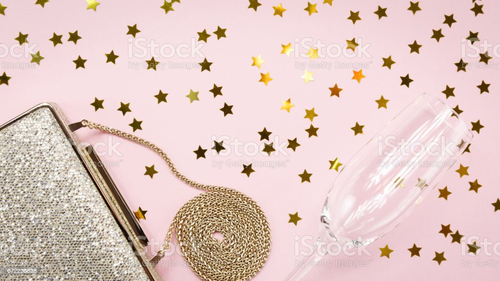 Festive evening golden clutch and champagne glass with star sprinkles on pink. Holiday and celebration background. Luxury accessories and party concept stock photo