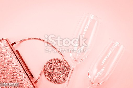 1078252566 istock photo Festive evening golden clutch and two champagne glasses on pink. Holiday and celebration background. Luxury accessories and party concept . Living coral theme - color of the year 2019 1081152134