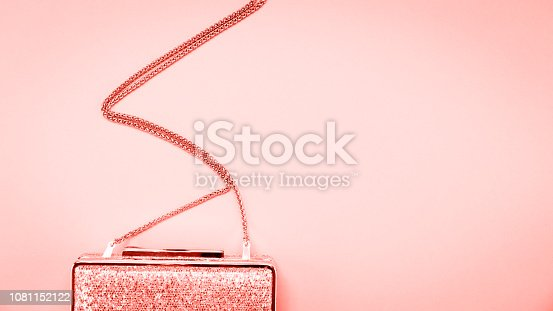 1078252566 istock photo Festive evening golden clutch on pink. Holiday and celebration background. Luxury accessories and party concept . Living coral theme - color of the year 2019 1081152122