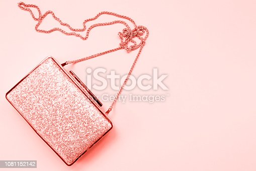 1078252566 istock photo Festive evening golden clutch on pink. Holiday and celebration background. Luxury accessories and party concept . Living coral theme - color of the year 2019 1081152142