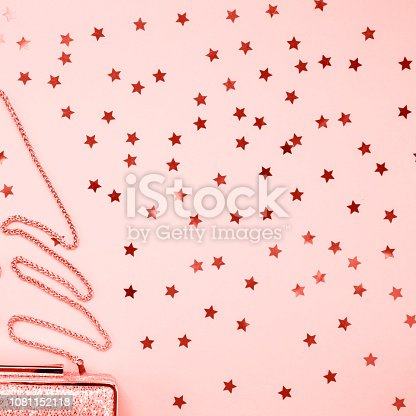 1078252566 istock photo Festive evening golden clutch with star sprinkles on pink. Holiday and celebration background. Luxury accessories and party concept . Living coral theme - color of the year 2019 1081152118