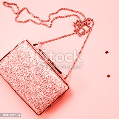 1078252566 istock photo Festive evening golden clutch with star sprinkles on pink. Holiday and celebration background. Luxury accessories and party concept . Living coral theme - color of the year 2019 1081152124