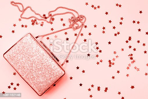 1078252566 istock photo Festive evening golden clutch with star sprinkles on pink. Holiday and celebration background. Luxury accessories and party concept . Living coral theme - color of the year 2019 1081152146