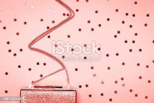 1078252566 istock photo Festive evening golden clutch with star sprinkles on pink. Holiday and celebration background. Luxury accessories and party concept . Living coral theme - color of the year 2019 1081152148