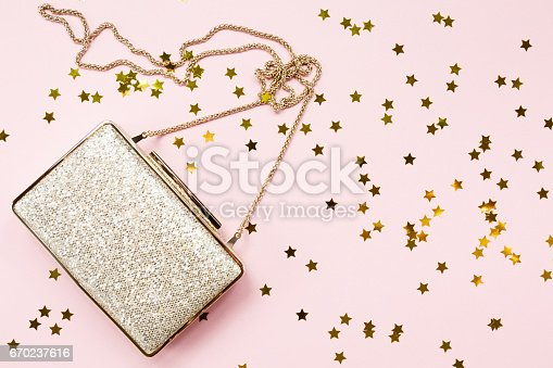 istock Festive evening golden clutch with star sprinkles on pink. Holiday and celebration background. Luxury accessories and party concept 670237616