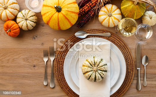 istock Festive Fall Thanksgiving dinner table place setting home decorations. Plates, silverware, cloth napkin, placemat, white wine and ornamental squash on rustic wooden tabletop. Holiday entertaining dinner parties. 1054102340