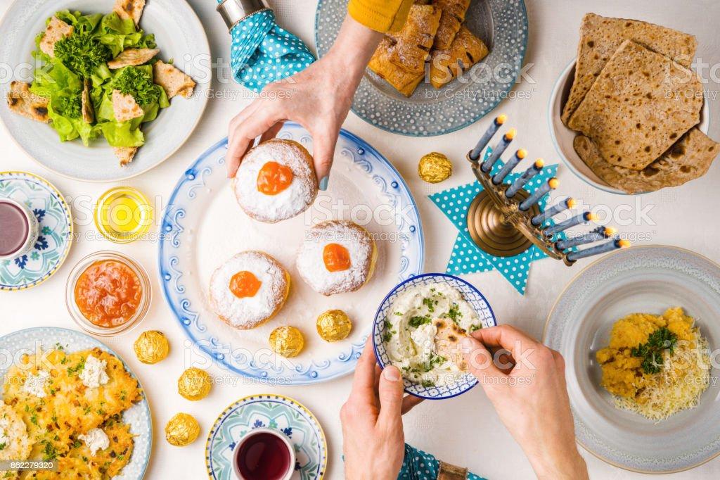 Festive feast on Hanukkah, table setting, hands over table stock photo