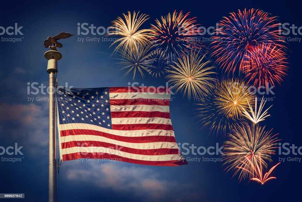 Festive fireworks display with American flag against dark night sky stock photo