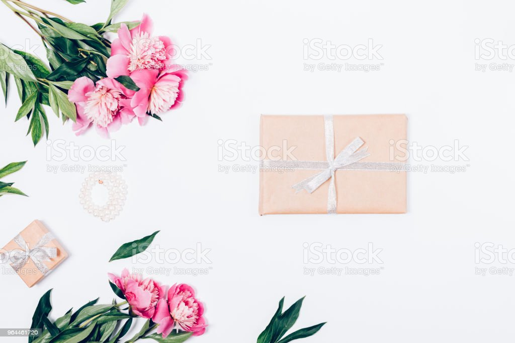 Festive flat lay composition with peonies, pearls and presents. Top...
