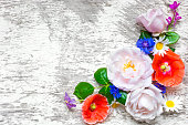 istock Festive flower composition on the white wooden background. top view. 807819332