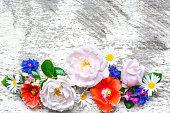 istock Festive flower composition on the white wooden background. top view 807819470