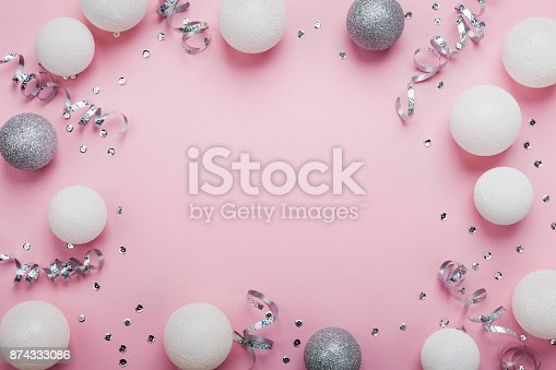 istock Festive frame made of christmas balls and sequins on pink table top view. Fashion background. Flat lay. Party mockup. 874333086