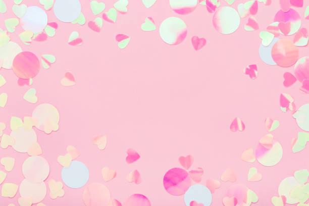 Festlicher Rahmen aus schillernden bunten Konfetti funkelt auf rosa Pastell Hintergrund. – Foto