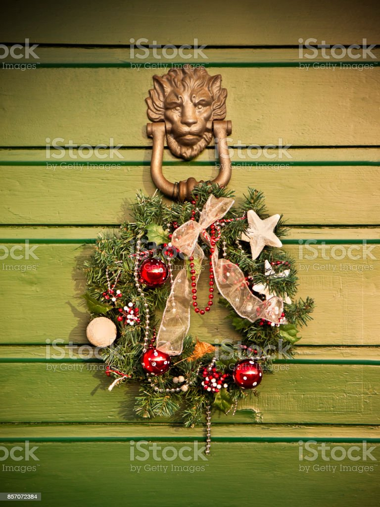 Festive garland Christmas hanging on a old wooden door stock photo