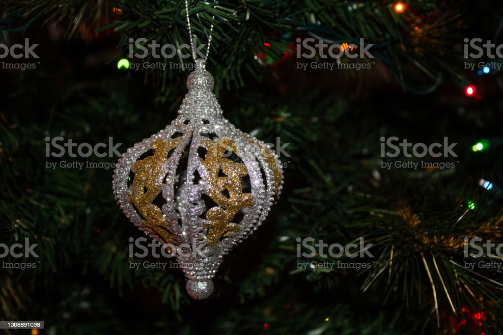 An Evergreen Christmas.Festive Gold And Silver Christmas Ornament Hanging On An