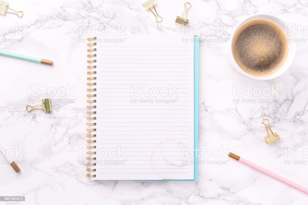 Festive golden stationary and coffee on white marble background. Feminine job, gender equality, home office and career concept. Copy space stock photo
