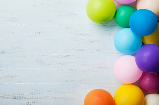 istock Festive greeting card. Heap of colorful balloons on blue wooden table top view. Birthday or party background. Flat lay style. 831732794