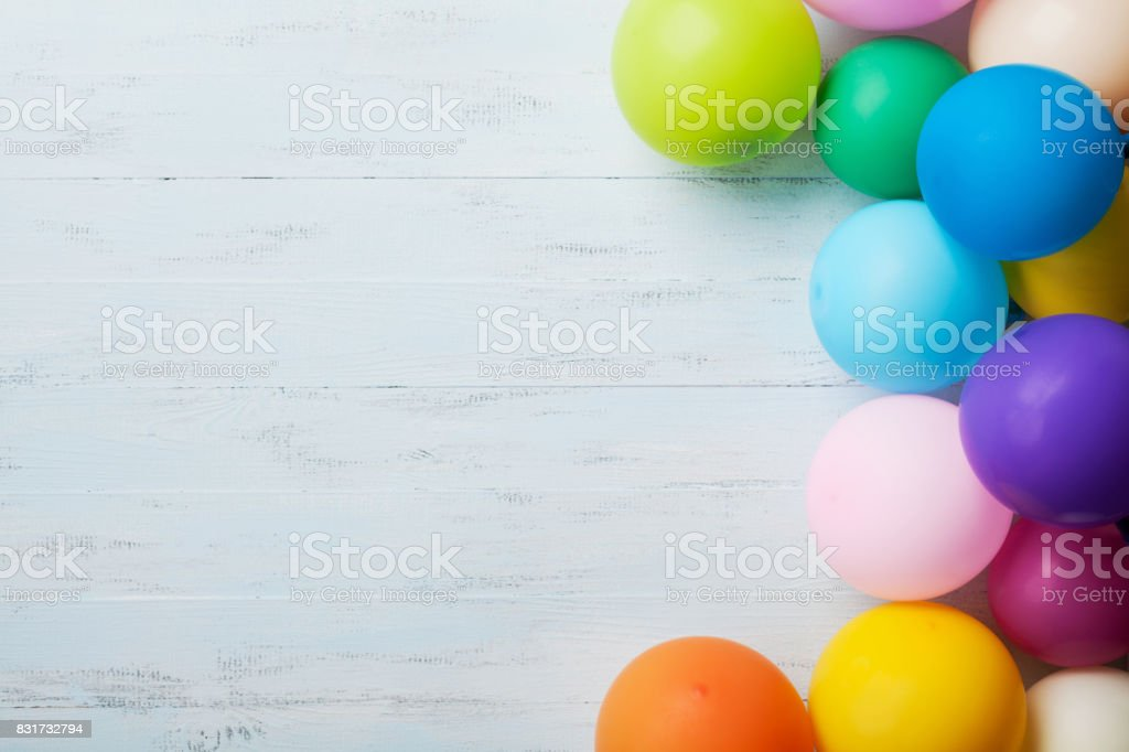 Festive greeting card. Heap of colorful balloons on blue wooden table top view. Birthday or party background. Flat lay style. stock photo