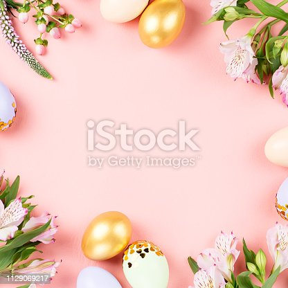 Festive Easter background with decorated eggs, flowers, candy and ribbons in pastel colors on pink background