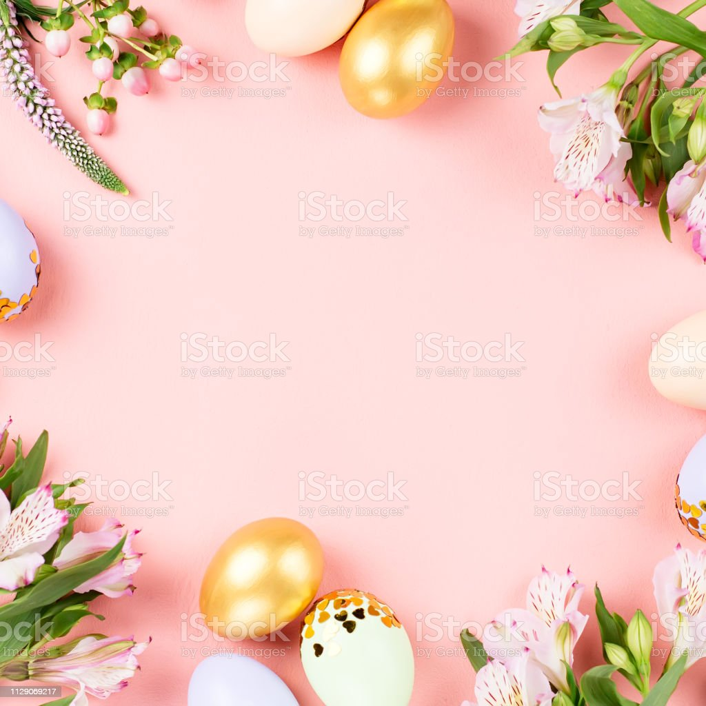Festive Happy Easter background with decorated eggs, flowers, candy and ribbons in pastel colors on pink. Copy space stock photo