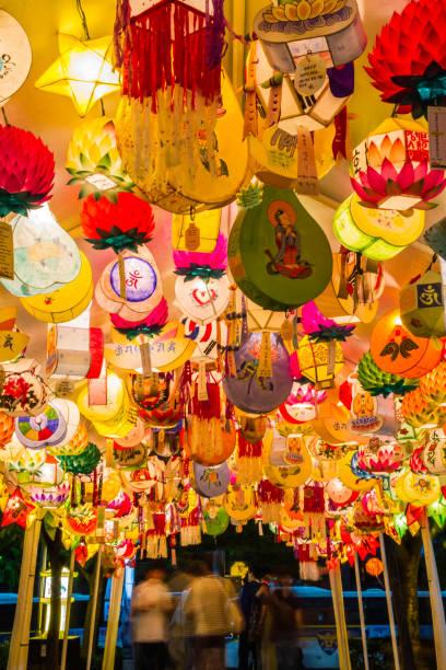 festive illuminated lanterns hanging over a walking path - festival delle lanterne cinesi foto e immagini stock