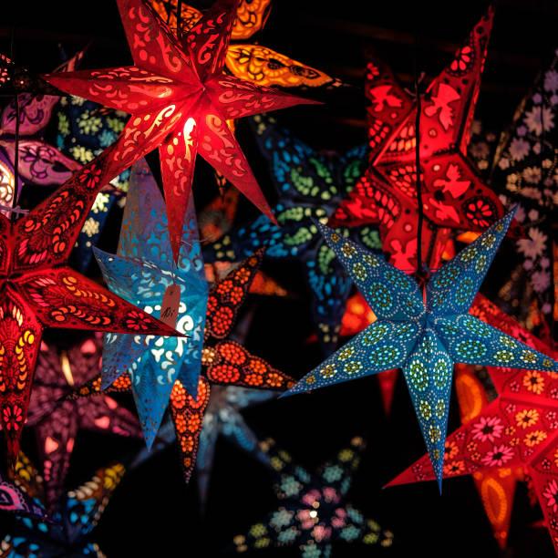 Festive lightning decorations, colorful star lanterns hanging on european Christmas market. stock photo