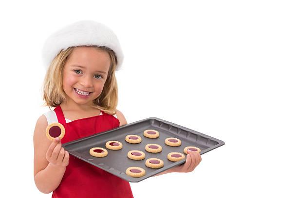 festliche kleine mädchen holding frische kekse - aufstrich weihnachten stock-fotos und bilder