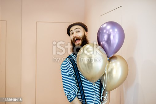 istock Festive man with balloons indoors 1155648418