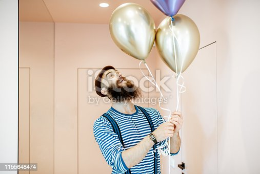 istock Festive man with balloons indoors 1155648474