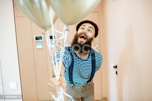 istock Festive man with balloons indoors 1155648510